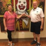 A man and a woman stand in front of a painting of a clown with red hair and large smile.
